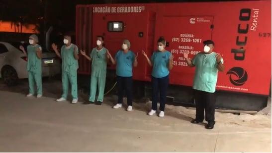 Pastor e profissionais de saúde louvam e oram em frente a hospital de campanha